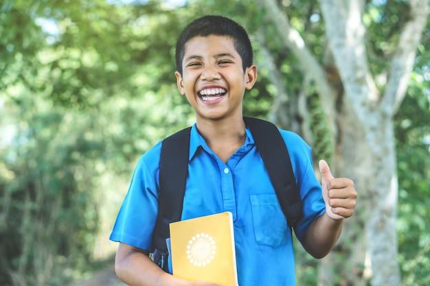 Étudiant garçon asiatique retour à l'école en riant dans un parc Photo Premium