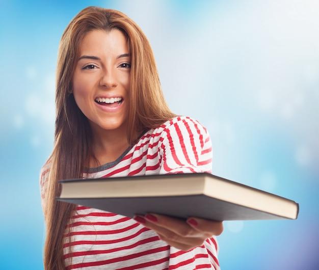 Étudiant heureux femme avec un livre dans la main Photo gratuit
