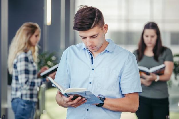 Étudiant Homme Lisant Dans La Bibliothèque Photo gratuit