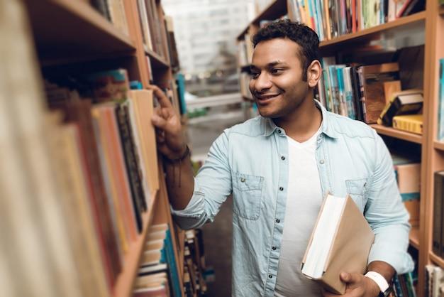 Étudiant indien ethnique dans l'allée du livre de la bibliothèque Photo Premium