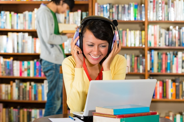Étudiant - jeune femme dans la bibliothèque avec ordinateur portable et casque d'apprentissage Photo Premium