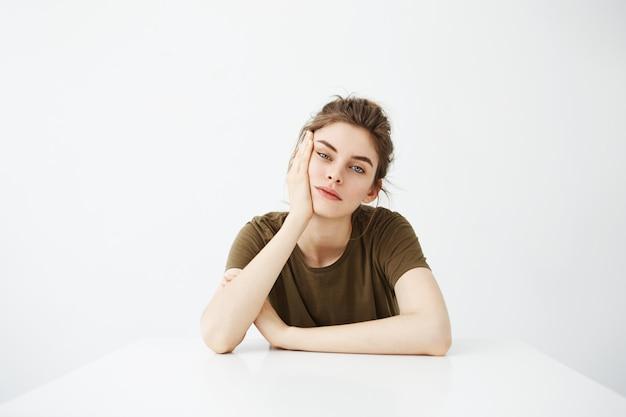 Étudiant De Jeune Femme Fatiguée S'ennuie Avec Chignon Assis à Table Photo gratuit