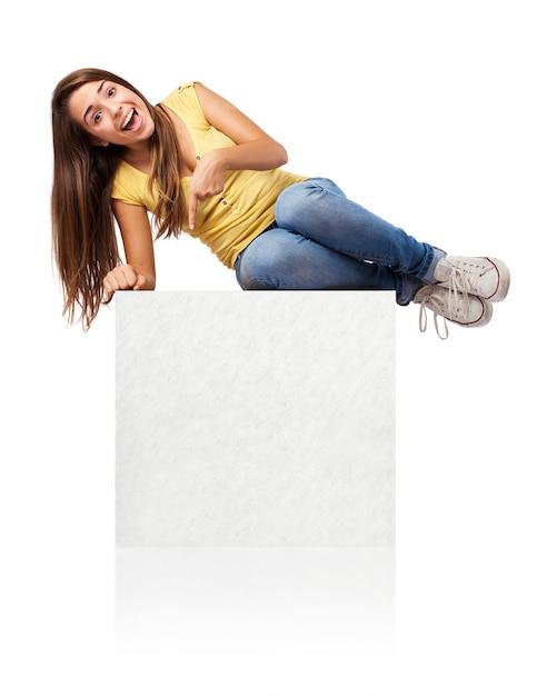 Étudiant joyful couché sur une affiche vide Photo gratuit