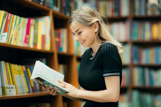 Étudiant Lisant Un Livre Dans La Bibliothèque Photo Premium