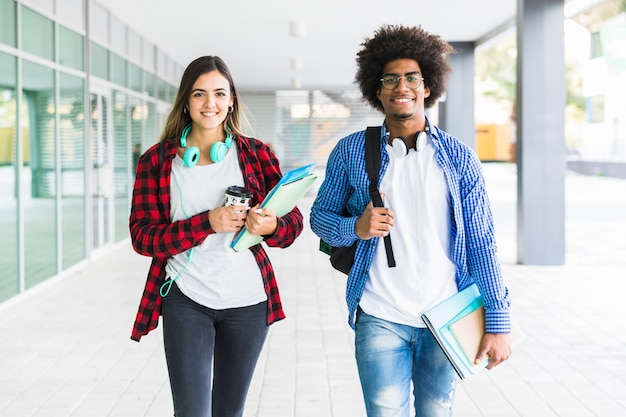 Étudiant masculin et féminin, tenant des livres à la main, marchant dans le couloir d'université Photo gratuit