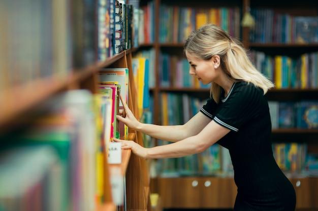 Étudiant à La Recherche De Livres Dans Une Bibliothèque Photo Premium