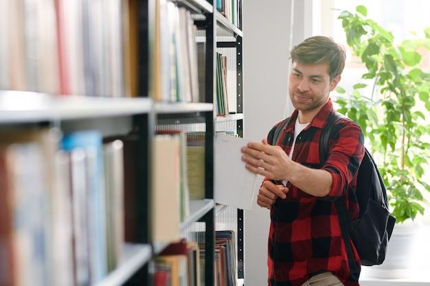 Étudiant Avec Sac à Dos En Prenant L'un Des Livres De L'étagère Dans La Bibliothèque Du Collège Photo Premium