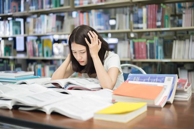 Étudiant Soumis à Une Pression Mentale Alors Qu'il Lisait Un Livre Préparant Un Examen Dans Une Bibliothèque Universitaire. Photo Premium