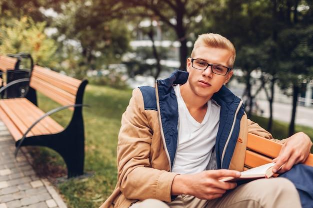 Étudiant universitaire avec livre de lecture de sac à dos marchant dans un parc en automne assis sur un banc Photo Premium