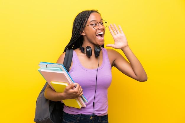 Étudiante adolescente afro-américaine avec de longs cheveux tressés sur un mur jaune isolé criant avec la bouche grande ouverte Photo Premium