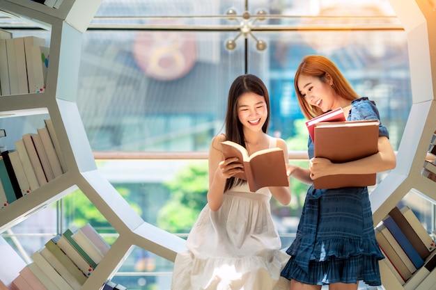 Étudiante Asiatique Lire Un Livre De Texte Dans La Bibliothèque De Son Université Photo Premium