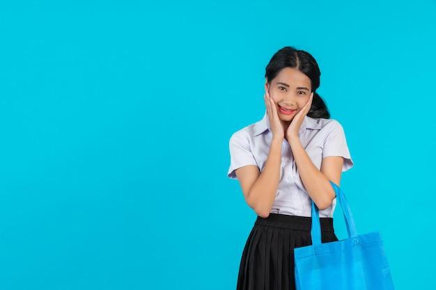 Une étudiante asiatique qui tourne un sac en tissu et montre divers gestes sur un bleu. Photo gratuit