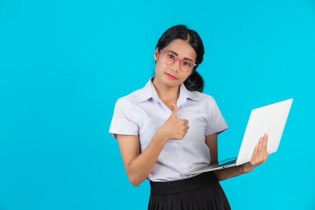 Une étudiante asiatique tenant son cahier sur un bleu. Photo gratuit