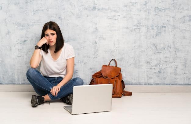 Étudiante assise sur le sol avec une expression triste et déprimée Photo Premium
