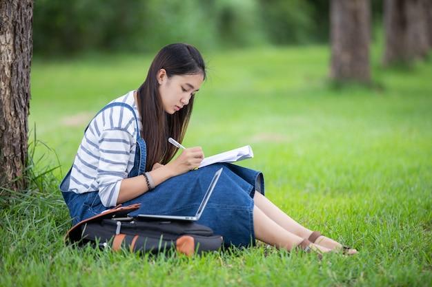 Étudiante belle fille asiatique tenant des livres et souriant et apprentissage et éducation sur parc en été pour se détendre Photo Premium