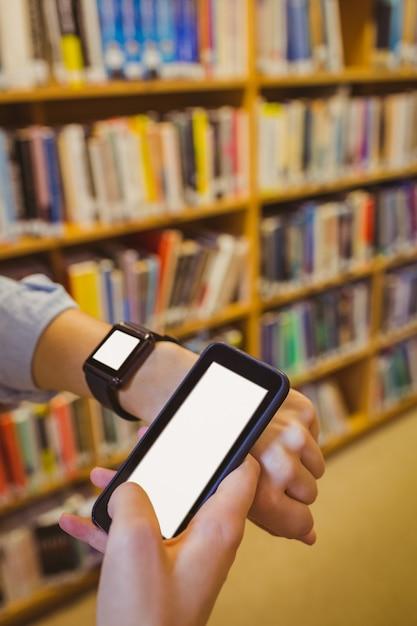 Étudiante brune utilisant sa montre intelligente et son smartphone dans une bibliothèque Photo Premium
