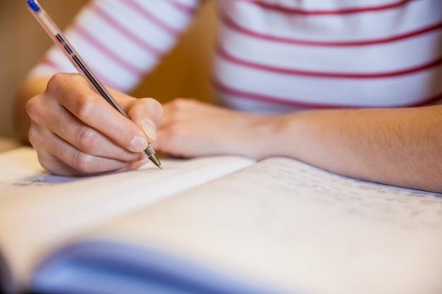 Étudiante écrivant des notes à l'université Photo Premium