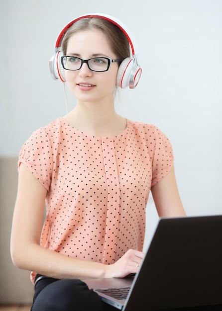 Une étudiante Est Assise Avec Un Ordinateur Portable Sur Ses Genoux, écoutant De La Musique Et Apprenant. Photo Premium