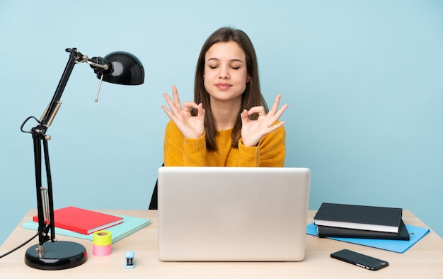 Étudiante étudiant Dans Sa Maison Sur Le Mur Bleu Dans Une Pose Zen Photo Premium