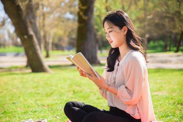 Étudiante étudiante étudie ses notes dans le parc Photo gratuit