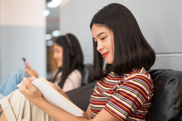 Une étudiante lit un livre à la bibliothèque Photo Premium