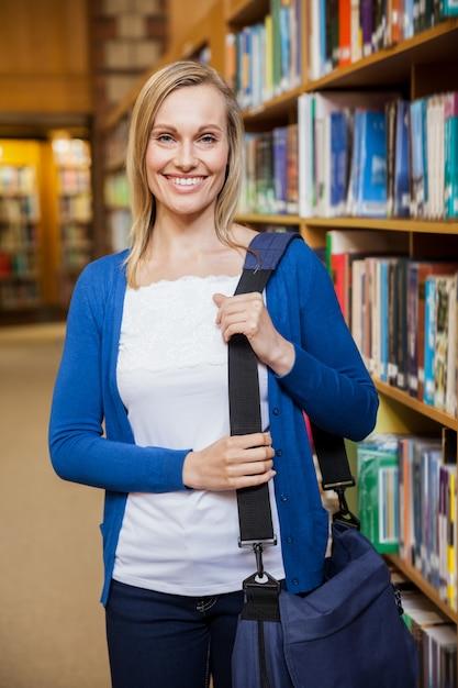 Étudiante souriante posant dans la bibliothèque de l'université Photo Premium