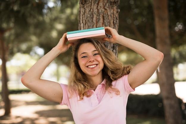 Étudiante tenant des livres au-dessus de la tête Photo gratuit