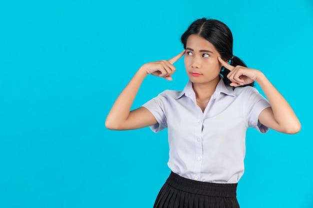 Étudiantes asiatiques effectuant divers gestes sur un bleu. Photo gratuit