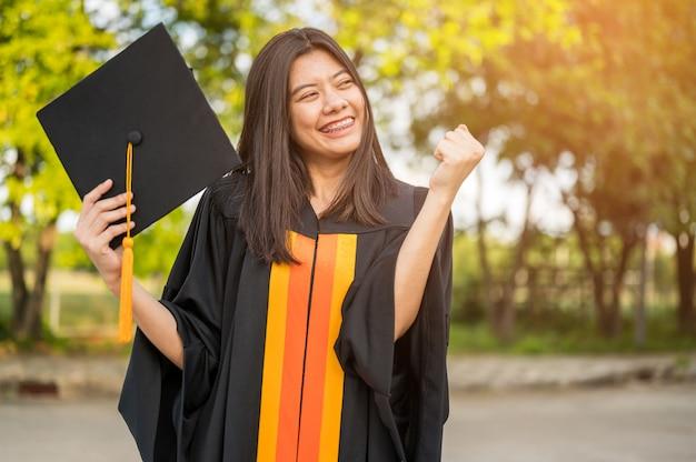 Les étudiantes aux cheveux longs portant des robes à volants noirs exprimant leur joie après l'obtention de leur diplôme à l'université. Photo Premium