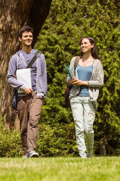 Étudiants amis marchant avec sac à bandoulière et tenant le bloc-notes Photo Premium