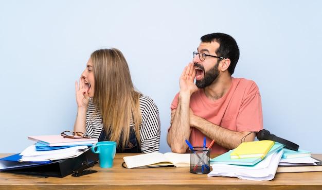 Étudiants avec beaucoup de livres criant avec la bouche grande ouverte sur le côté Photo Premium