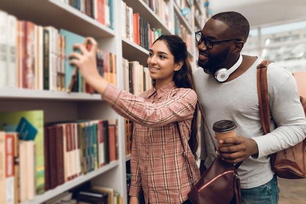 Les étudiants cherchent des livres dans la bibliothèque. Photo Premium