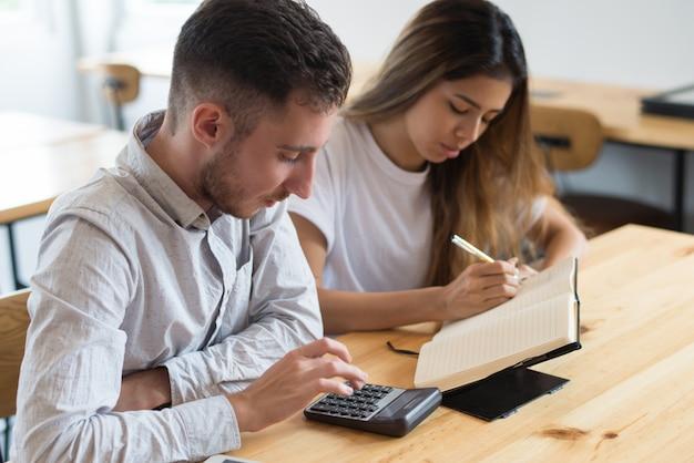 Étudiants ciblés utilisant une calculatrice et étudiant ensemble Photo gratuit