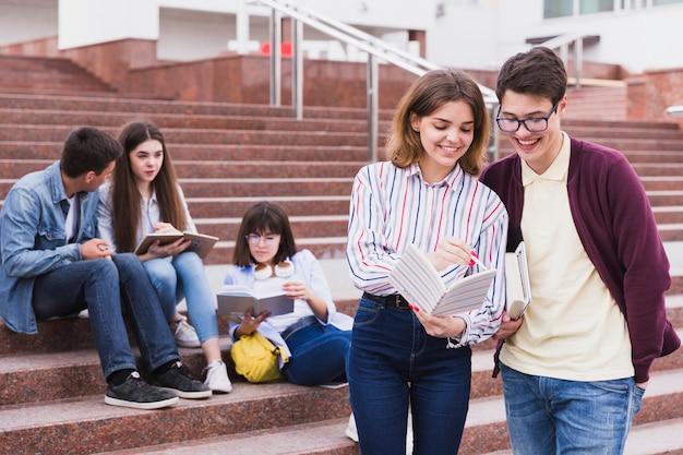 Étudiants debout avec cahier ouvert Photo gratuit