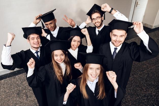 Les étudiants en manteaux sont heureux qu'ils terminent leurs études Photo Premium