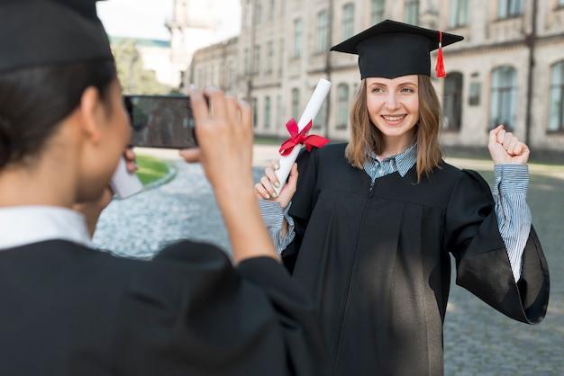 Étudiants prenant des photos les uns des autres à la remise des diplômes Photo gratuit