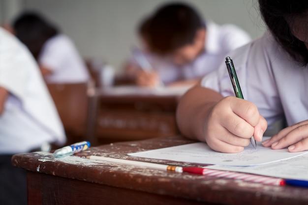 Les étudiants qui écrivent répondent à un examen en classe Photo Premium