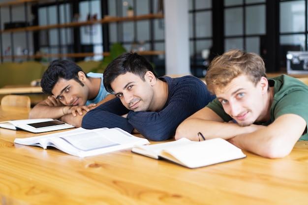 Étudiants reposant sur un bureau avec des manuels et regardant la caméra Photo gratuit
