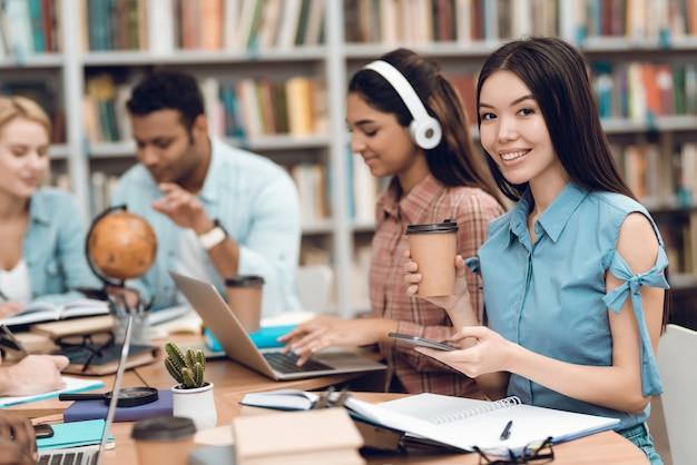 Les étudiants sont assis à table dans la bibliothèque. Photo Premium