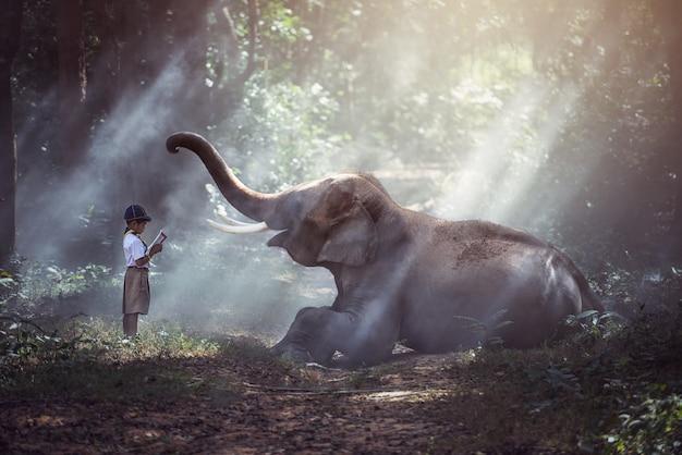 Étudiants en thaïlande rurale lisant des livres avec des éléphants, surin, thaïlande. Photo Premium