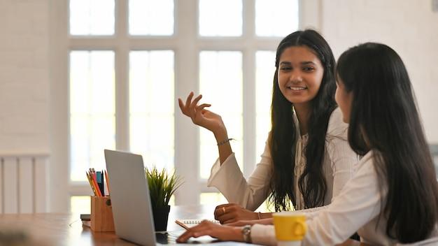 Les étudiants De L'université Sont Assis Ensemble Devant Un Ordinateur Portable Au Bureau. Photo Premium