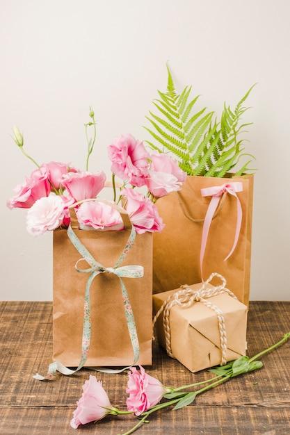 Eustoma fleurs dans un sac en papier brun avec une boîte cadeau sur une surface en bois contre un mur blanc Photo gratuit