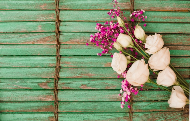 Eustoma et des fleurs de souffle de bébé sur fond de volet en bois vert Photo gratuit