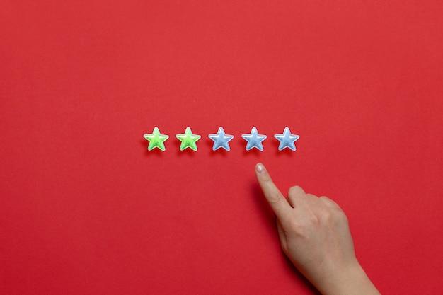 Évaluation De La Qualité De Service Et De La Prestation De Services. La Main Féminine Laisse Une Note De Deux étoiles Sur Cinq Possible Sur Un Fond Rouge. Photo Premium