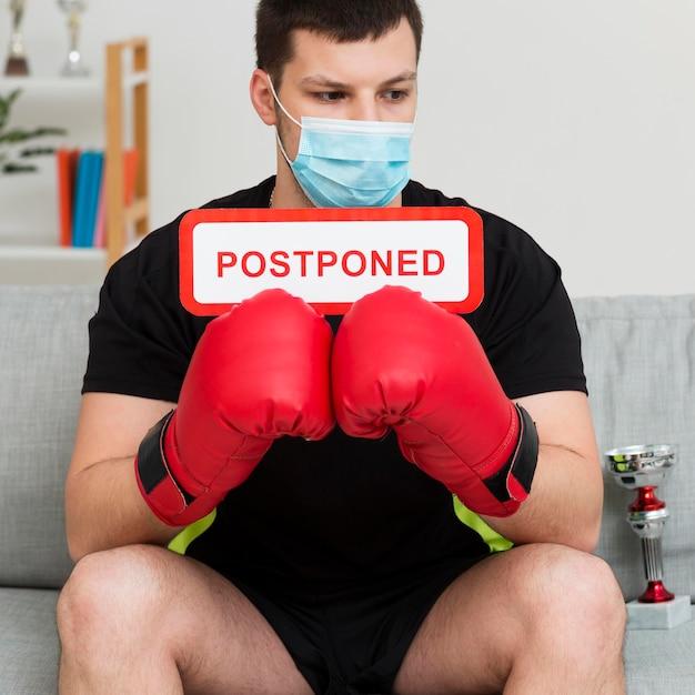 Événement De Boxe Reporté Message Détenu Par Un Homme Portant Un Masque Médical Photo gratuit