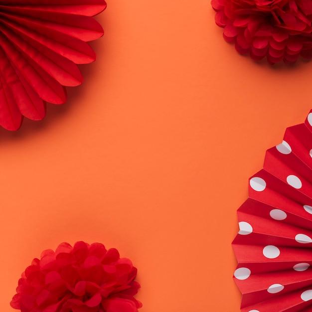 Éventail de fleurs et de papier artificiels décoratifs rouge vif sur fond orange Photo gratuit