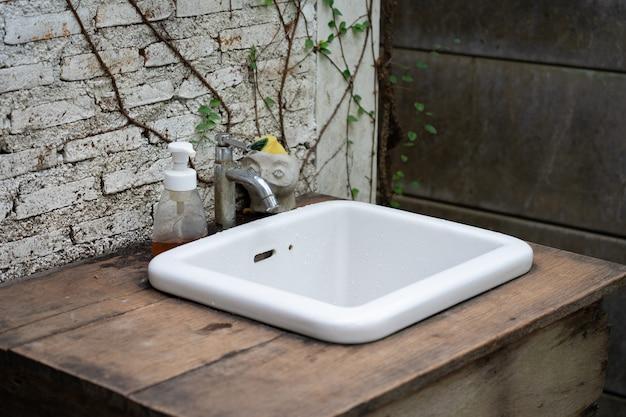 Évier en céramique blanche dans le jardin, jardin vintage Photo Premium