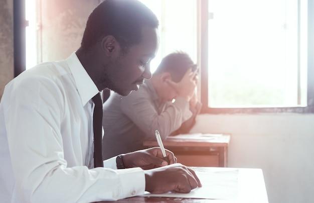 Examen avec homme africain faisant test pédagogique avec le stress en salle de classe. Photo Premium