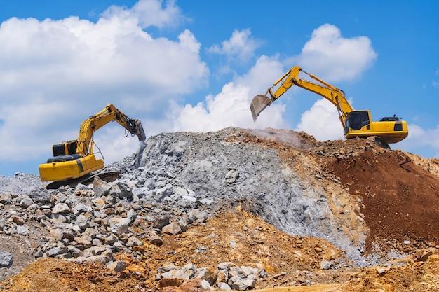 Excavateurs et machine de concassage de pierre de l'exploitation minière sous un ciel bleu avec des nuages Photo Premium
