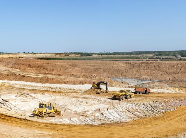 Excavatrice chargeant du sable dans des camions à benne. extraction de sable dans la carrière. Photo Premium